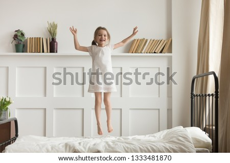 Photo of Happy funny little child girl in motion jumping on bed alone flying in air feeling joy, cheerful cute active kid having fun playing laughing in bedroom after waking up, good morning children concept