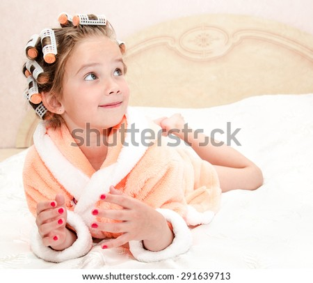 Happy funny little girl with manicure and hair curlers in bathrobe lying on bed