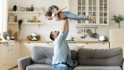 Happy funny little kid girl flying in fathers arms family having fun in modern studio apartments, loving single daddy holding lifting cheerful pre-school daughter playing plane enjoy playtime at home