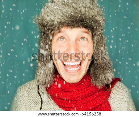 Happy funny male portrait looking snowflakes falling down wearing hat and scarf in december season