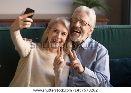 Happy funny mature senior couple taking selfie looking at smartphone, cheerful elder old grandparents having fun holding phone make snapshot self portrait laughing showing peace sign sitting on sofa