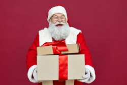 Happy funny old bearded Santa Claus wears costume holds many presents, Merry Christmas giftboxes wrapped with red ribbon, laughing standing with gift boxes having fun isolated on red xmas background.