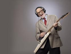 Happy funny senior man playing electric guitar
