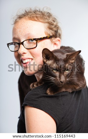 Happy funny teenage girl holding brown oriental cat. Curly blonde hair. Wearing glasses. Expressive face. Studio shot isolated on grey background.
