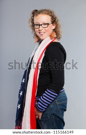 Happy funny teenage girl with curly blonde hair. Expressive face. Wearing glasses. Holding american flag. Studio shot isolated on grey background.