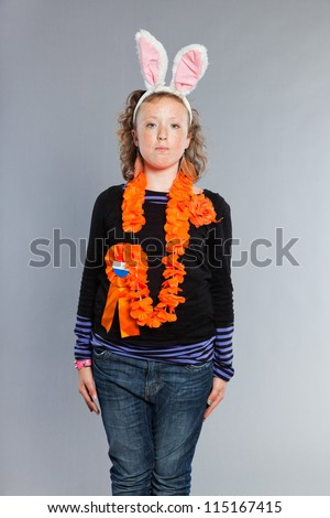 Happy funny teenage girl with curly blonde hair. Wearing bunny ears and party decoration. Expressive face. Studio shot isolated on grey background.