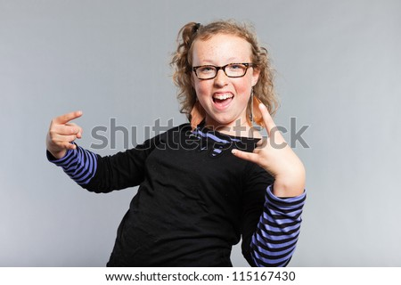 Happy funny teenage girl with curly blonde hair. Wearing glasses. Expressive face. Studio shot isolated on grey background.