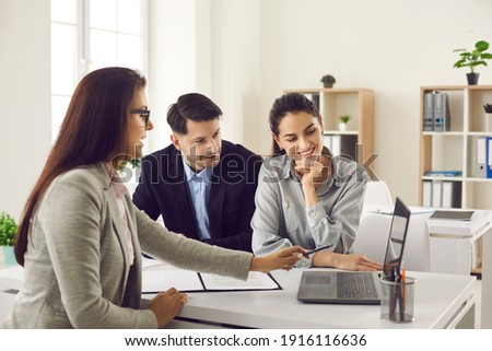 Happy future house buyers meeting real estate agent. Professional realtor talking to clients and offering flats options on computer. Smiling couple consulting bank worker or loan broker at her office