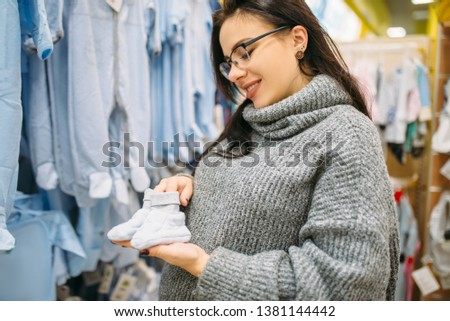 Happy future mother buys childrens clothes
