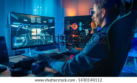 Happy Gamer Playing First-Person Shooter Online Video Game on His Powerful Personal Computer. Room and PC have Colorful Neon Led Lights. Cozy Evening at Home.
