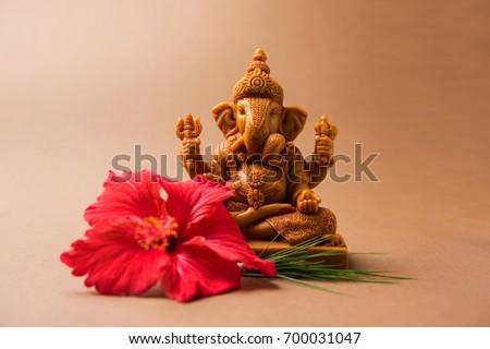 Happy Ganesh Chaturthi Greeting Card showing photograph of lord ganesha idol with pooja or puja thali, bundi laddu/modak, durva and hibiscus or jasvand flower  Stock photo ©