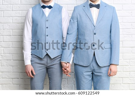 Happy gay couple holding hands together on brick wall background #609122549