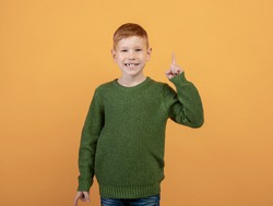 Happy ginger kid cute school boy in knitted green sweater pointing finger up over yellow studio background. Smiling redhead boy aiming up, having great idea or found creative solution