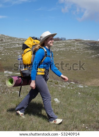 Happy gir in hatl with yellow backpack walking into the distance Stok fotoğraf ©