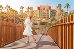happy girl admires beautiful view of the Madinat Hotel and Mall. Travel and vacation in Dubai and United Arab Emirates