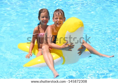 Happy girl and boy swim at the children inflatable toy in the swimming pool