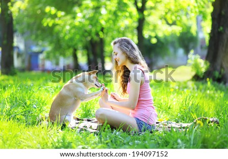 Happy girl and dog having fun in summer sunny park, dog gives paw owner