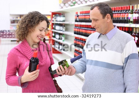 happy girl and  elderly man in shop with wine bottles in hands