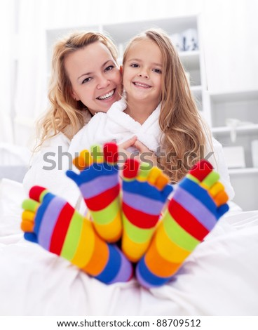 Happy girl and woman at home after bath wearing colorful socks