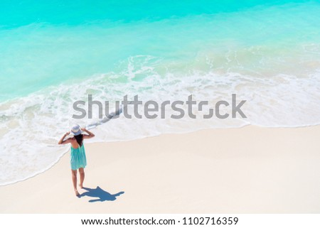 Happy girl at beach having a lot of fun in shallow water from above view