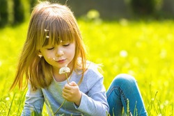 Happy girl blowing dandelion flowers