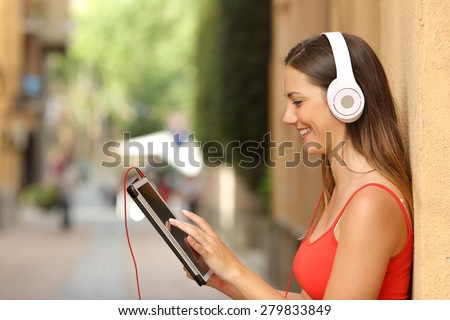 Happy girl browsing a tablet and listening to the music with headphones leaning on a wall in the street