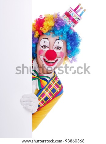 Happy girl clown in birthday cake hat holding the blank board