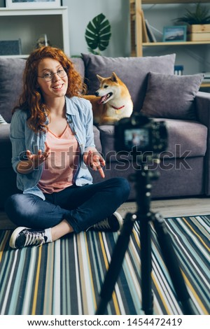 Happy girl creative vlogger recording video with adorable dog at home sitting on floor talking stroking cute pet. Social media and blogging concept. #1454472419