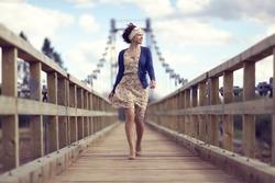 happy girl dress runs over the bridge