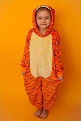 Happy girl dressed as a tiger cub. A child in a kigurumi in the form of a tiger. Happy girl in striped orange pajamas. Cute tiger cub on a yellow background. Lifestyle concept.  Rest, relax and enjoy
