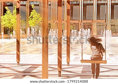 happy girl enjoying hot autumn day in city landscape. Modern city architecture landmark. Dancing fountain in apartment building patio. Summer in city. Relaxation area in urban cityscape background