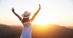 happy girl enjoying nature at sunset in summer