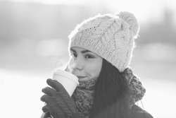 Happy girl enjoys aromatic coffee drink.White clear takeaway paper cup from a cafe.Place your logo on cup.Pretty young woman in winter clothes