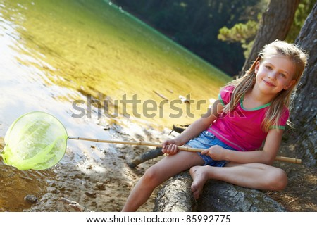 Happy girl fishing at lake