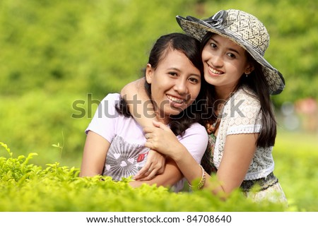 happy girl friends smiling together in green nature