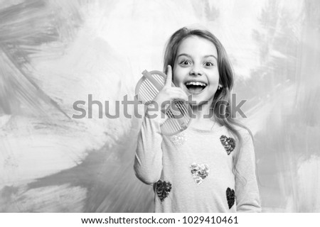 Happy girl having idea on colorful abstract wall. Baby model with orange sunglasses in fashionable clothes pointing finger up. Eureka concept. Child fashion