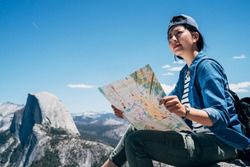 happy girl hiker sitting holding paper map finding direction on top of mountain. young tourist resting on the big rock looking on guidebook with blue sky. amazing nature view yosemite national park.
