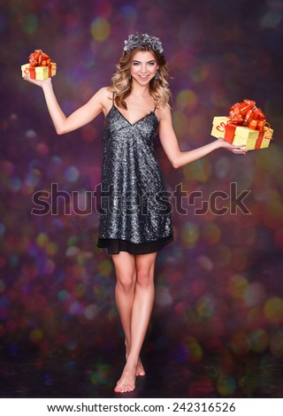 Happy girl holding a box with gifts. barefoot woman in a smart dress. colored background