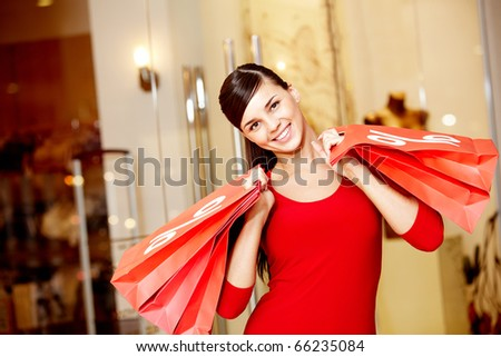 Happy girl holds red paperbags with symbol of sale and looking at camera