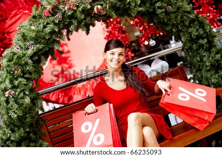 Happy girl holds red paperbags with symbol of sale in market