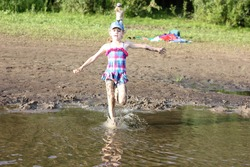 happy girl in a bright swimsuit runs into the river, splashes and splashes around, active holidays with children on the beach in summer