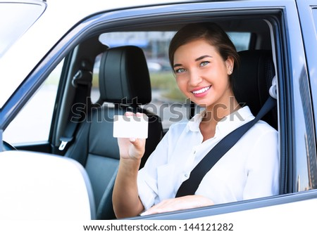 Happy girl in a car showing an empty white card for your message