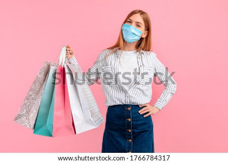 happy girl in a medical mask on her face, posing with shopping bags and looking at the camera on a pink background. Shopping, quarantine