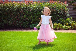 Happy girl in a pink skirt with hydrangea on the meadow in the garden