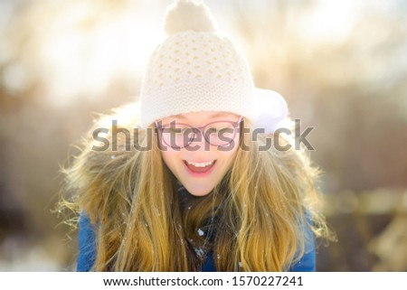 Happy girl in a snowy park throws snowflakes and has fun. Winter fun.