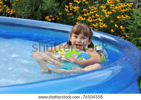 Happy girl in a swimming pool on backyard. Summer time, hot day.