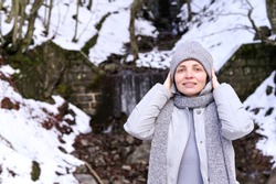 Happy girl in a warm jacket and hat stands in a snowy forest. The concept of tourism and travel. Copy space.