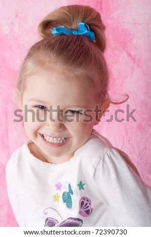 Happy girl in a white sweater, smiling.  She has a blue bow in her hair and there is a pink background