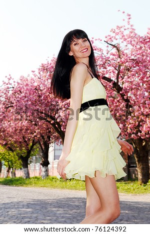 Happy girl in a yellow dress running down the avenue