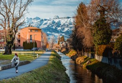 Happy girl in Alps mountains in Liechtenstein. Medieval Red House, calm narrow mountain river and jogging track, residential buildings, blue sky and snow-capped mountains. Liechtenstein, Vaduz